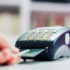 Hand slipping credit card into a card reading device; copyright: PantherMedia/Mitar gavric