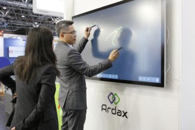 Ein Mann im Anzug zeichnet etwas auf einen Touch-Bildschirm
