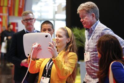 eine junge Frau zeigt etwas auf einem Tablet anderen Besuchern