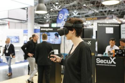 Eine junge Frau trägt eine VR Brille auf einer Messe