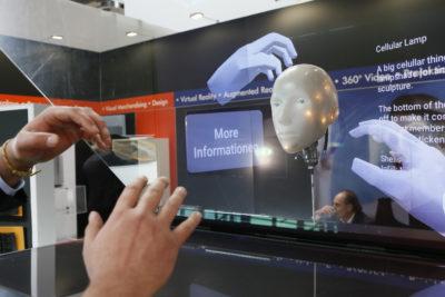 Zwei Hände steuern Bilder auf einem durchsichtigen Bildschirm