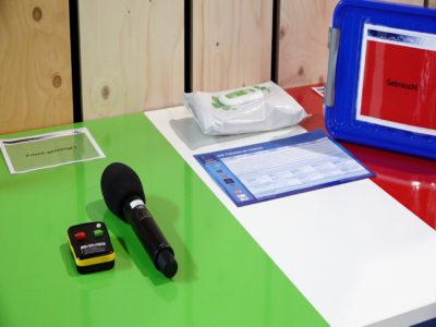 Ein Tisch ist in zwei Bereiche eingeteilt - desinzifiert und benutzt, Mikrofone liegen entsprechend in den Bereichen