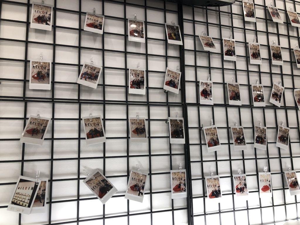 Ein schwarzes Gitter vor einer weißen Wand, an dem Polaroidfotos hängen