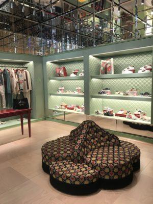 Eine moderne Boutique mit Waren in einem Regal und einer Sitzgruppe in der Mitte