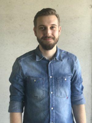 Ein lächelnder junger Mann im Jeanshemd