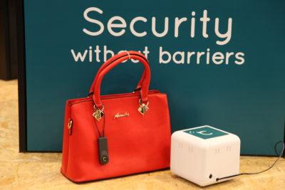 Bild: rote Handtasche neben EAS-System; Copyright: iXtenso