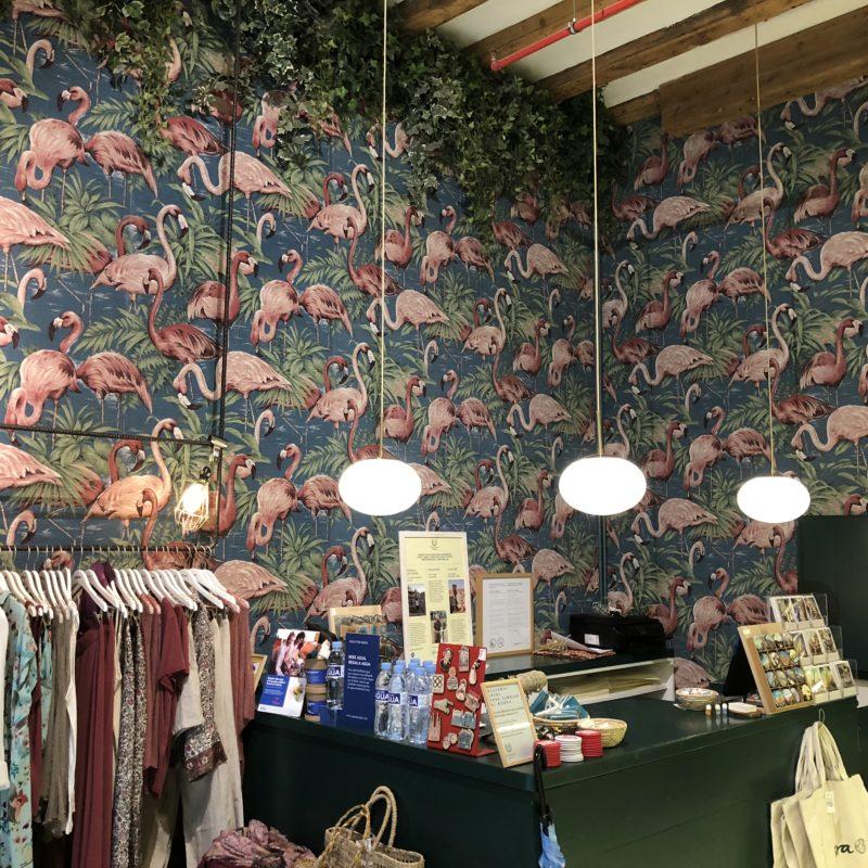 Ein Kleiderständer links neben der Kasse. Im Hitnergrrund: eine Tapete mit rosa Flamingos