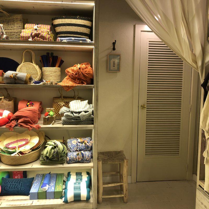 Links ein Regal mit verschiedenen Artikeln, rechts eine Tür und ein Vorhang