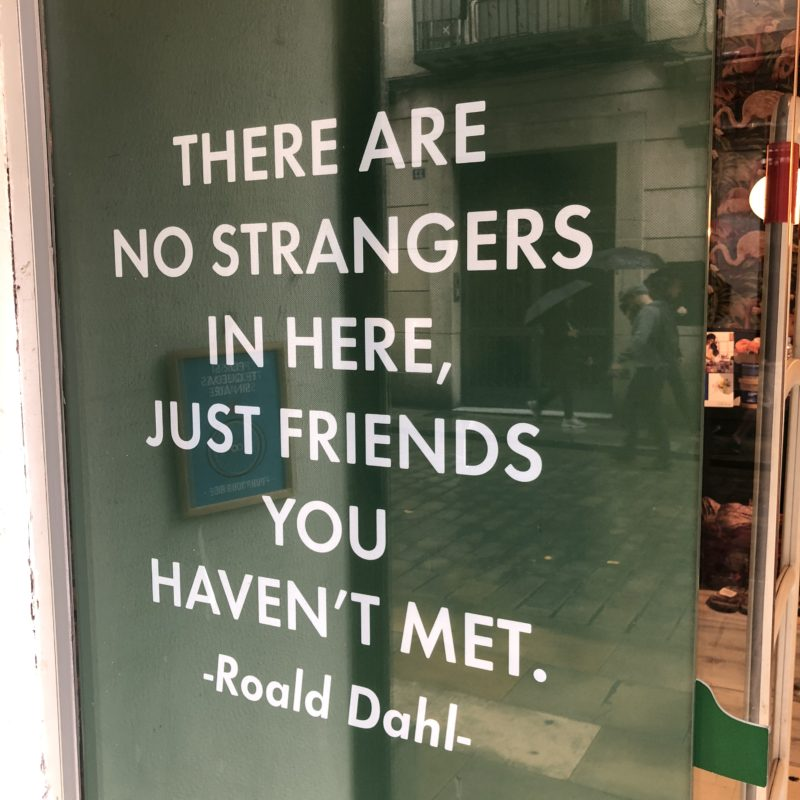"A glass wall with the inscription ""There are no strangers in here, just friends you haven't met"""