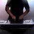 Ein DJ an seinem Pult in vernebeltem Raum mit Hintergrundlicht