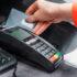 Sales person swiping credit card through card reader; copyright: panthermedia.net / AndrewDemenyuk