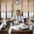 Mann im Büro mit Kasse und Wust an Kassenbons; copyright: panthermedia.net / stokkete