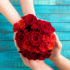 Two people hold a bouquet of red roses