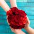 Zwei Personen halten einen Strauß roter Rosen