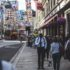 Man on a busy shopping street stops and looks at his smartphone; copyright: Arthur Edelman/Unsplash