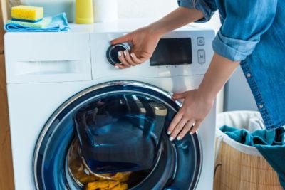 Jemand stellt eine Waschmaschine an