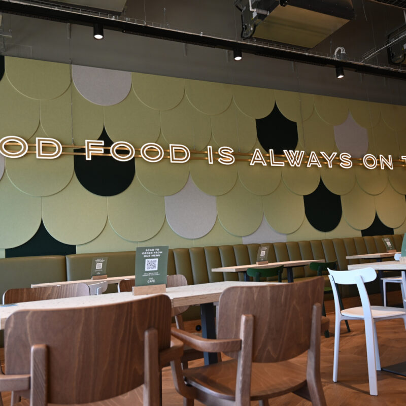 """The phrase """"Good Food is always on the menu"""" in neon letters on the wall of a café"""