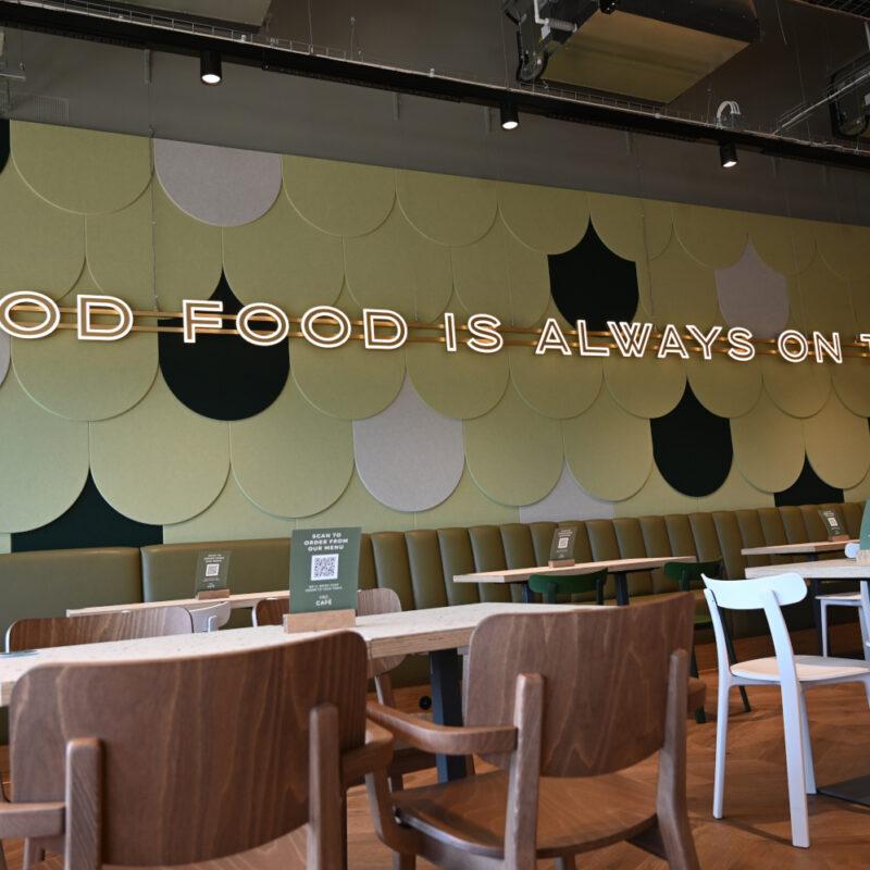 """Der Satz """"Good Food is always on the menu"""" in Leuchtschrift an der Wand eines Cafés"""