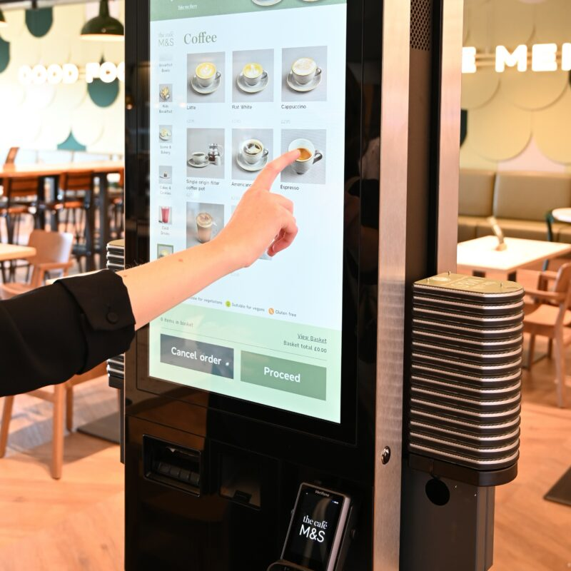 A person operates a digital self-service stele in a café