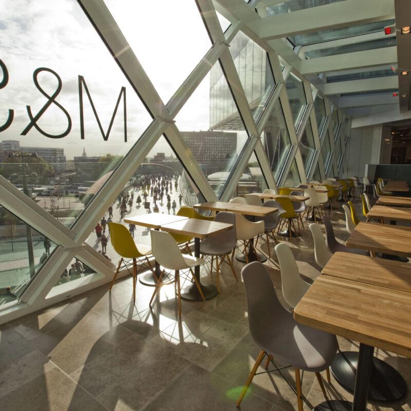 Tische und Stühle vor einem riesigen Fenster mit Blick hinaus