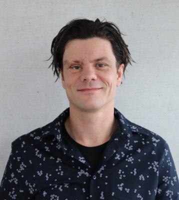 Mann mit längeren dunklen Haaren und gemustertem Hemd lächelt in die Kamera; copyright: Universität Innsbruck