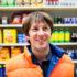 Ein Mann in einer orangenen Weste steht lächelnd vor einem Supermarktregal