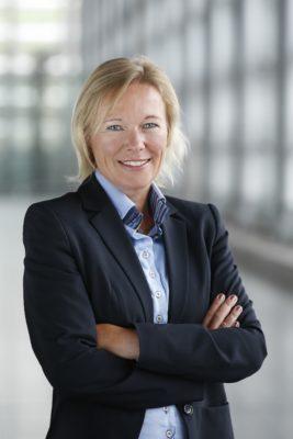 Ein blonde Frau im Blazer mit verschränkten Armen lächelt in die Kamera