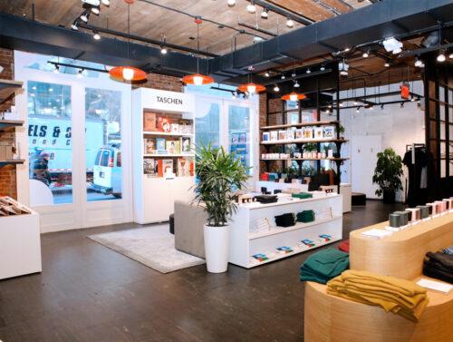 Verkaufsraum mit Stahl, Holz und Beleuchtungselementen im Industriedesign. © Neighbourhood GoodsHeller Verkaufsraum mit Mix an Büchern, Mode und Geschenkartikeln vor der Kassenzone, © Neighbourhood Goods