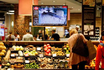 Obst- und Gemüsetheke bei REWE mit großem Bildschirm auf dem der Livestream läuft