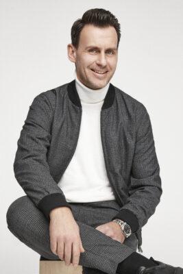 Mann in weißem Rollkragenpullover und grauer Jacke lächelt in die Kamera; copyright: s.Oliver