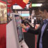 Man uses self service kiosk with touch screen; copyright: beta-web