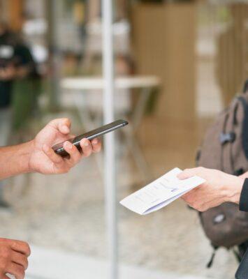 Jemand scannt mit sienem Handy einen QR-Code auf einem Zettel