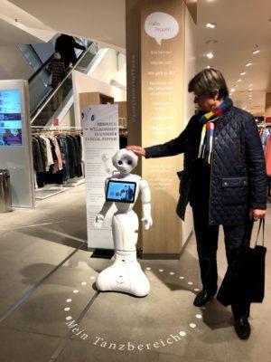 Eine Kundin im Modegeschäft streicht dem weißen kleinen Roboter Pepper über den Kopf;: copyright: Humanizing Technologies GmbH