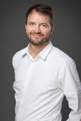 Mann in weißem hemd steht vor grauer Wand und lächelt in die Kamera; copyright: Scandit