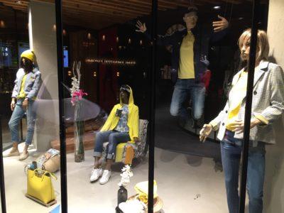 Schaufenster mit sitzenden und stehenden Schaufensterpuppen in gelb-blauer Kleidung; copyright: iXtenso/Pott
