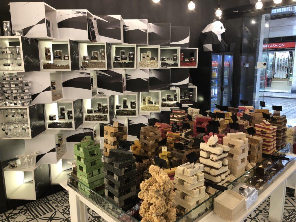Ein schwarzweißes Regal aus Würfeln mit Schokoladenblöcken auf Warentischen davor