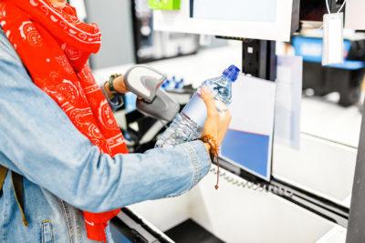 glückliche Frau kauft Flasche Wasser an Supermarkt-Selbstbedienungskasse; copyright: PantherMedia / frantic00