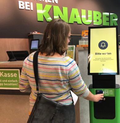 Eine Frau hält ein Smartphone an ein Terminal mit Lesegerät