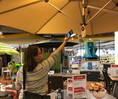 Frau mit Smartphone scannt Etikett an einem Sonnenschirm