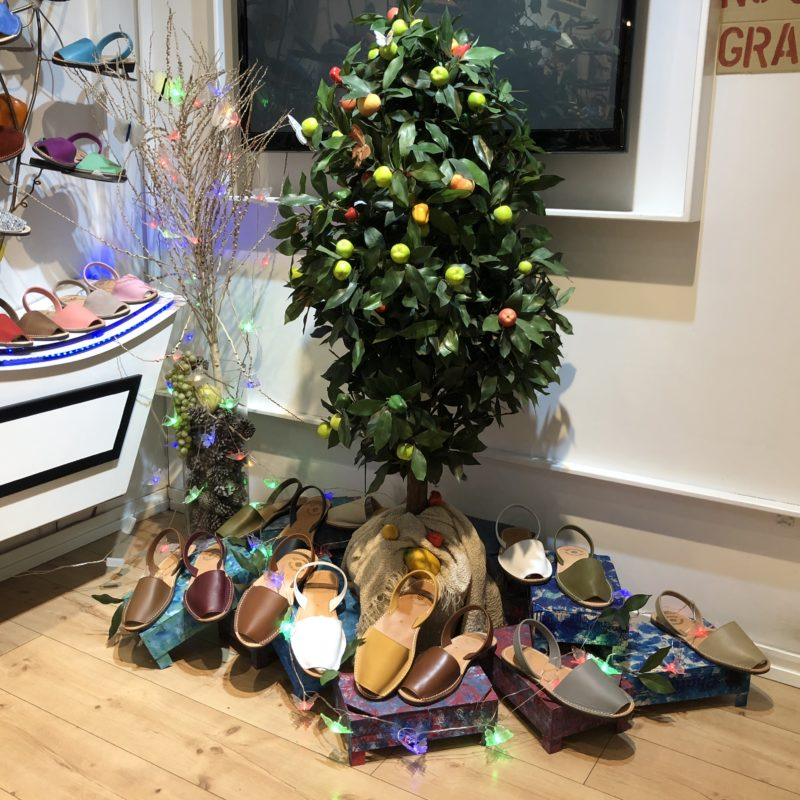A green plastic tree in a shop with shoes around it