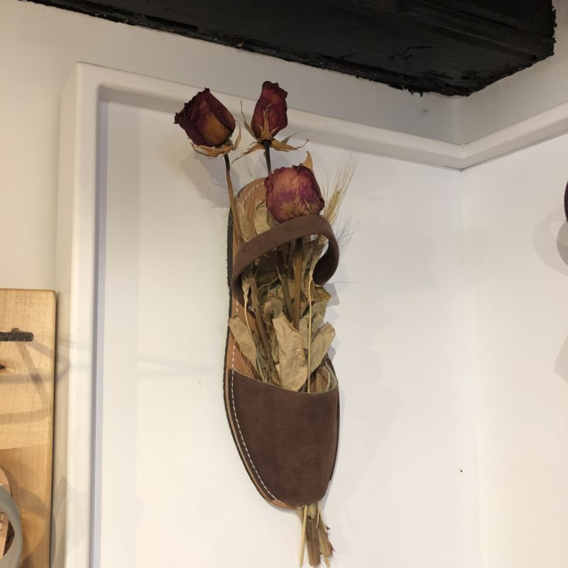 A sandal with the sole attached to the wall, with dry flowers inside