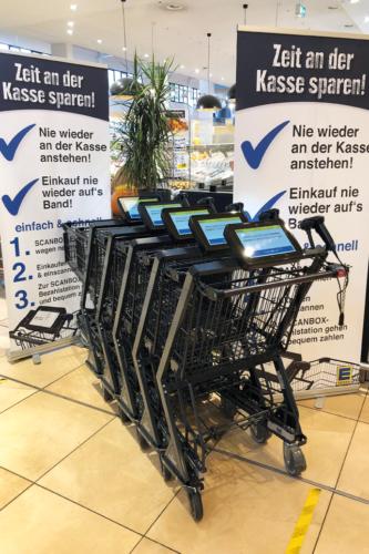 Einkaufswagen und Plakate an einem Supermarkteingang