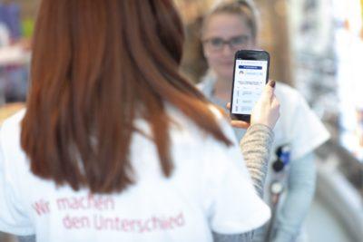 Mitarbeiter hält Smartphone, von hinten fotografiert; Copyright: Andy Ridder