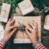 Von oben fotografierte Hände, die Geschenke verpacken