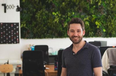 Ein junger Mann im Polohemd vor einem grünen Hintergrund