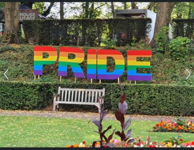 """Das Wort """"Pride"""", englisch Stolz, in großen regenbogenfarbenen Buchstaben in einem Park"""