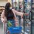 A women with a mask is looking at frozen foods in a supermarket