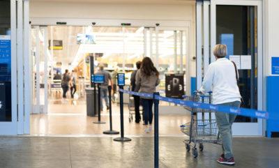 Kunden stehen in einer Warteschlange vor und in einem Geschäft mit viel Abstand