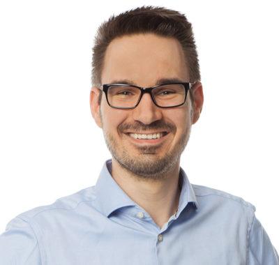 Ein junger Mann mit Brille und Hemd lächelt in die Kamera