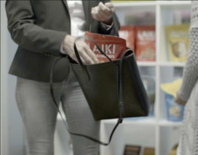 Eine Frau steckt beim Einkaufen etwas in ihre Handtasche
